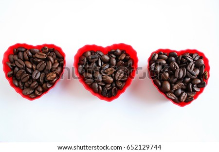 three heart shaped cups filled with coffee beans on a white background/heart beat/fast pumping hearts #652129744