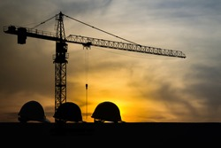 Three helmet silhouette at construction site with crane background and sunset