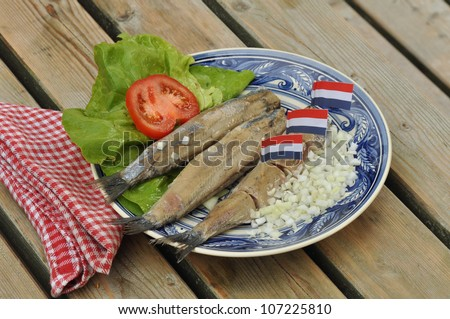 Three Herring fillets on plate with lettuce, chopped onions, and dutch flags
