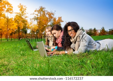 three high school students laying with laptops in the park