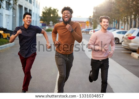 Three hip young adult male friends running for fun in a city road, front view, three quarter length