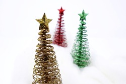 three holiday trees made from wire with stars on top, in yellow, green, and red.  Fake snow made from white wool.  Focus on front (yellow) tree and a blurry background.  white background.