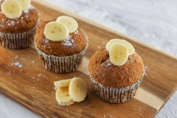 Three homemade banana muffins as illustration of easy recipe or food menu on wooden background