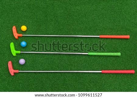 Three horizontal mini golf putters with three mini golf balls on artificial grass