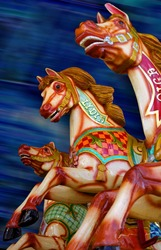 Three horses of a merry-go-round. Focus is on the middle horse.