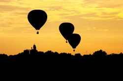 Three hot air balloons are silhouetted at sunset as the float above an Iowa landscape.