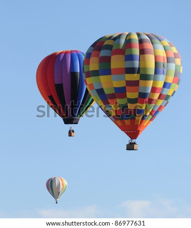 Three hot air balloons floating in the air