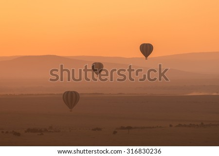 Three hot air balloons fly over the low hills of the African savannah. The aerial perspective makes the hills look different shades of purple, and the sky is bright orange in the pre-dawn light.