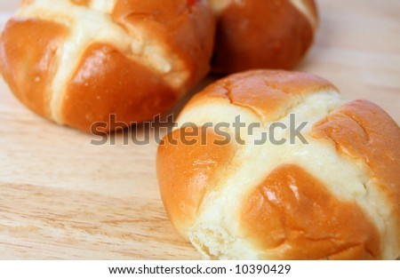 Three hot cross buns on a breadboard. The sweet breads are a traditional British favourite, especially at Easter.