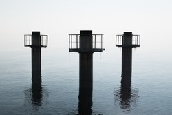 Three huge pillars of concrete emerge from the water against a strong diffused light, with reflections on water surface.