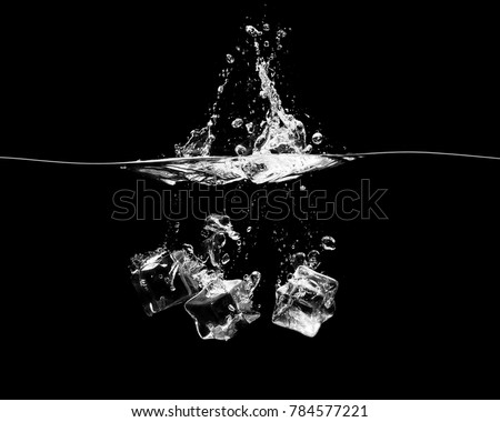 Three ice cubes falling into the water with a splash