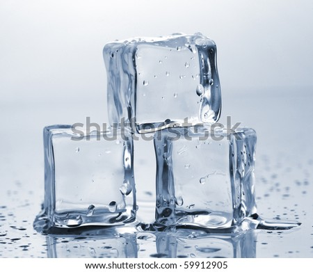 Three ice cubes on glass table - stock photo