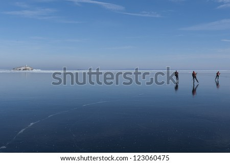 Three ice skaters on a big lake with crystal clear ice. V�¤ttern, V�¤stra G�¶taland, Sweden.
