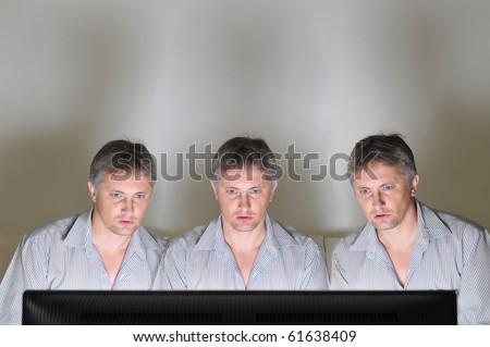 Three identical clones or triplets watching television or a computer screen together
