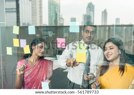 Three Indian employees sticking reminders on glass wall with business tasks and deadlines in the office