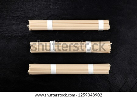 Three individually wrapped portions of udon noodles, shot from the top on a black background with a place for text