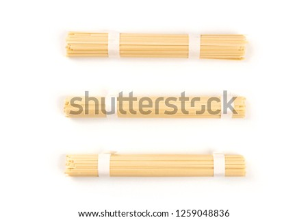 Three individually wrapped portions of udon noodles, shot from the top on a white background with a place for text
