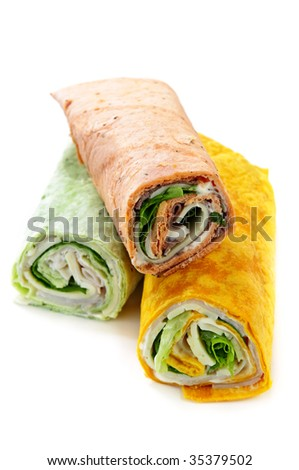 Three isolated multicolored tortilla wraps with meat and vegetables - stock photo