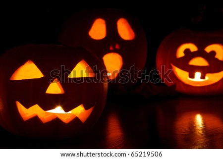 three jack-o-lantern pumpkins glowing in the dark