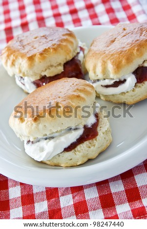 Three jam and cream scones on a white plate