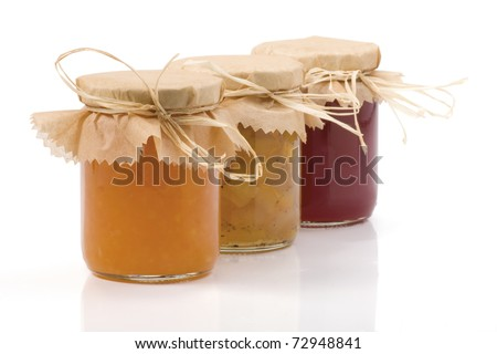 Three Jam jar isolated on a white background. Apples, cabbage-cardamom jam jar, Orange jam and Currant jam jar. With clipping path. Shallow DOF. Focused on the front.