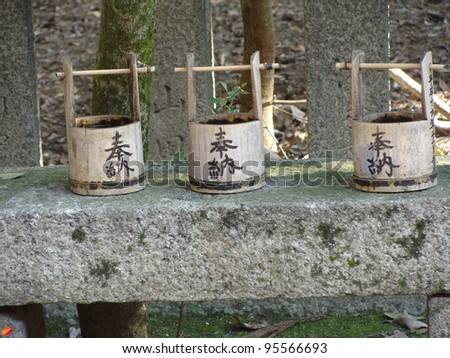 Three Japanese water carriers  on stone bench in a temple in Kyoto