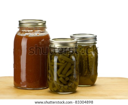 Three jars of home canned food tomato sauce pickles beans