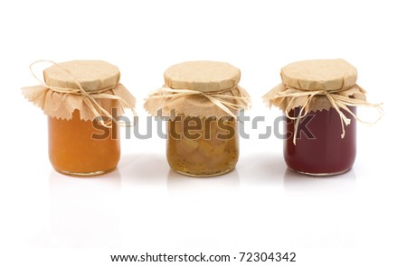 Three jars of jam isolated on a white background. Orange jam. Apples, cabbage and cardamom jam. Red Currant jam. - stock photo