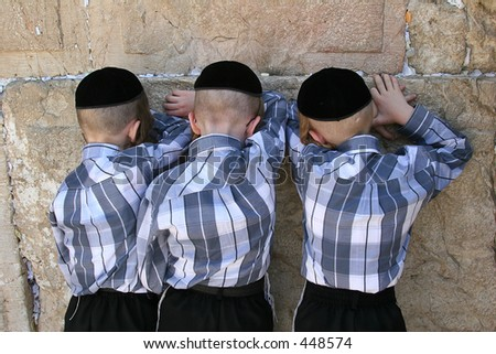 Three Jewish brothers praying at the wailing wall.