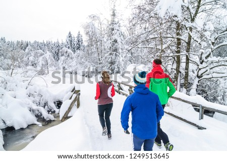 three joggers during running workout in wintry nature #1249513645