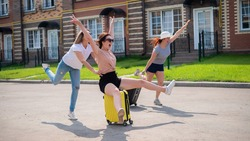 Three joyful Caucasian friends are having fun and chasing each other while riding a suitcase. Excited women go on a road trip. The brunette blonde and the redhead are going on vacation.