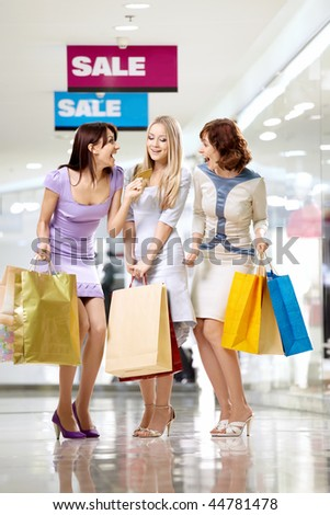 Three joyful girlfriends in shop with a credit card
