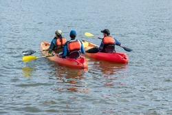 Three kayakers kayak on the Potomac River in Washington, D.C.