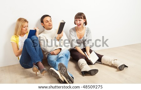 Three kidding students with books - one man and two women