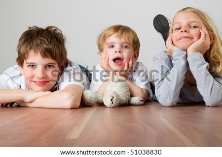 Three kids are lying on their bellies on the floor
