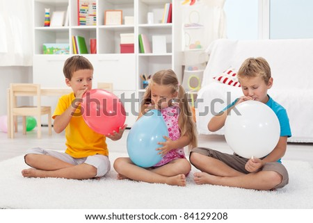 Three kids blowing large balloons sitting on the floor - stock photo