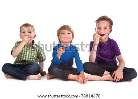 three kids eating sweets on white background