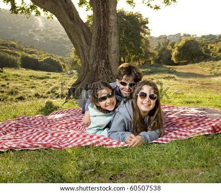 three kids having fun on a picnic outdoors
