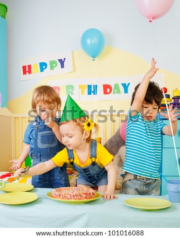Three kids having fun on the birthday party - two boys and one girl