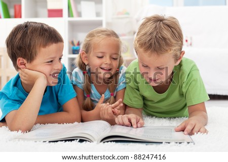 Three kids having fun reading a book laying on the floor