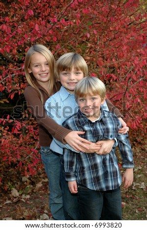 three kids in front of a burning bush