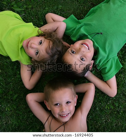 three kids laying in the grass