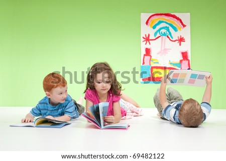 Three kids lying on floor reading books. On white and green.