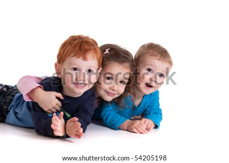 Three kids lying on floor together. Isolated on white