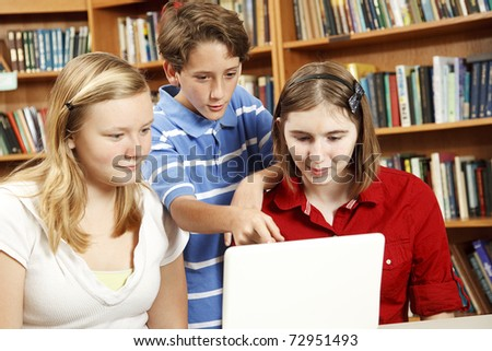 Three kids on the computer in the school library.