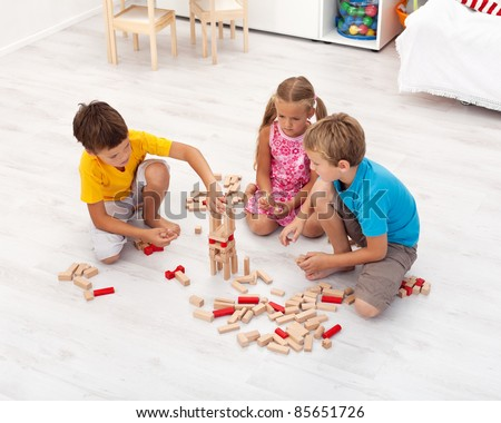 Three kids playing with wooden blocks in their room - top view