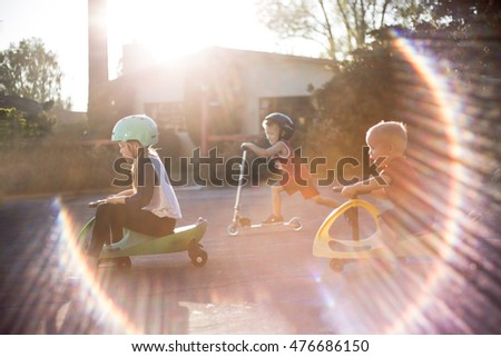 Three kids riding scooters and bikes with sun flare
