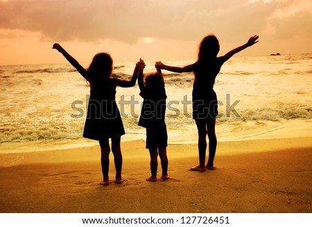 three kids silhouettes standing on beach at sunset