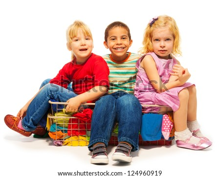 three kids sitting in the clothes basket - black boy and two blond girls