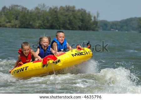 three kids tubing behind a boat